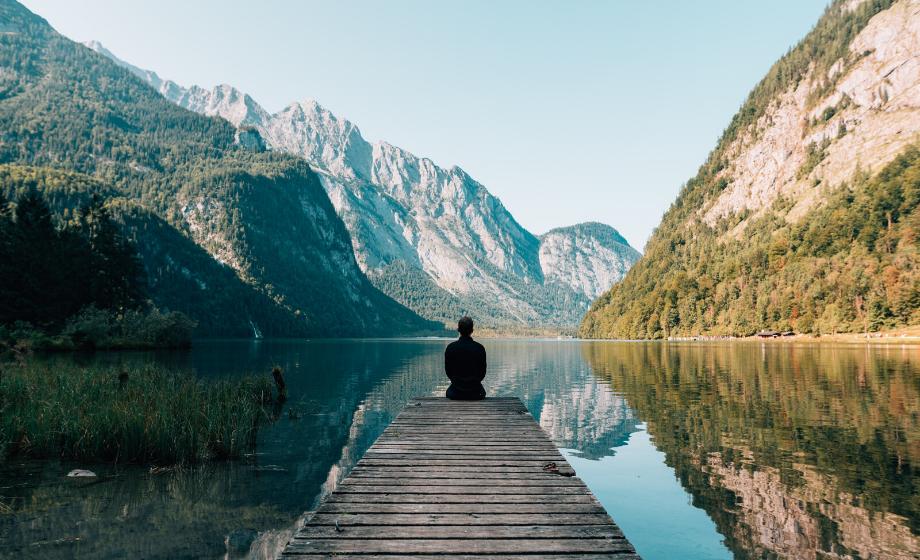Mann sitzt auf einem Steg am See in den Bergen