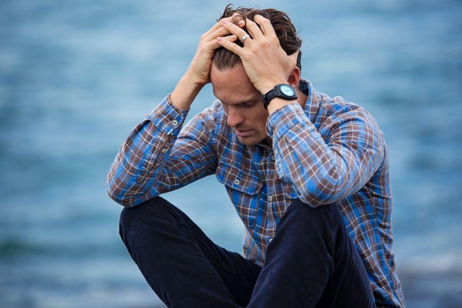 Mann sitzt alleine mit Händen im Haar und geneigten Kopf vor Wasser