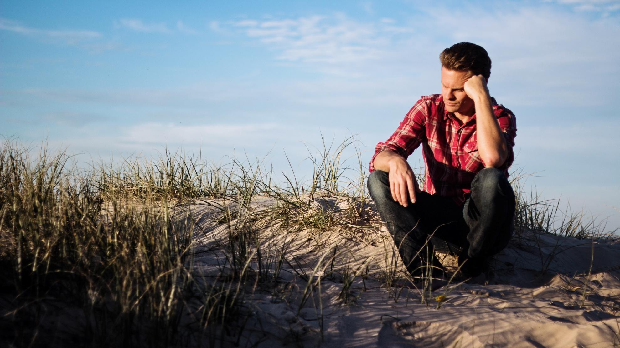 Ein Mann sitzt nachdenklich in der Natur