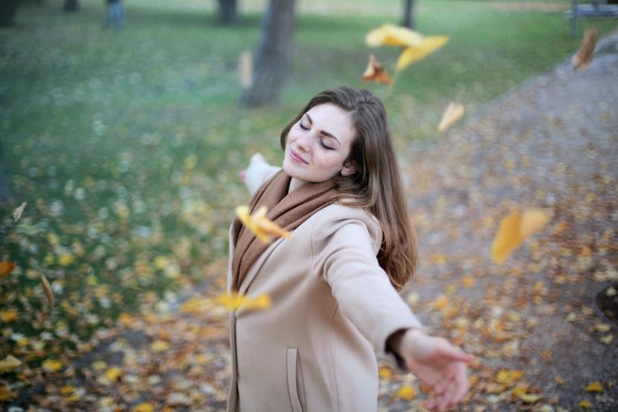Frau die fröhlich im Herbstlaubt steht